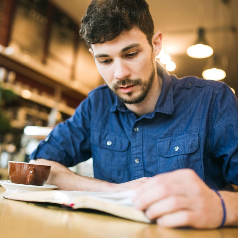 A young man studies the Bible at a coffee shop.