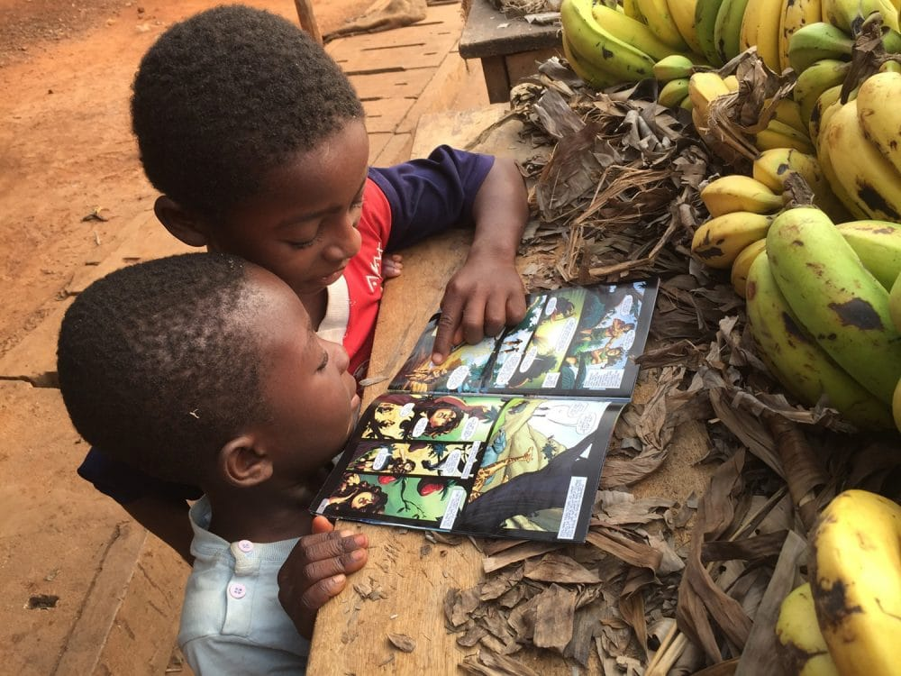Two young boys read The Story of Jesus comic.