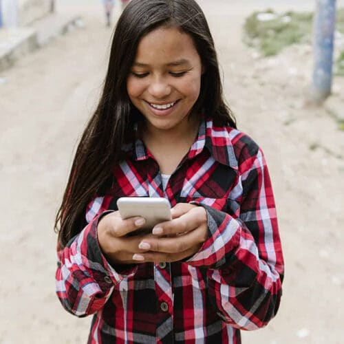 Young woman accesses resources on her cell phone.